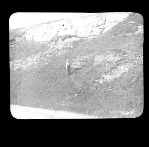 LDGSL/1088/AC/GB/66Black and white photograph of a geological feature in Frocester, by Ananda Kentish Coomaraswamy, [1890s-1900s].    The woman who is included in the scene for scale purposes could be Ethel Partridge, later Ethel Mairet, who became Coomaraswamy's first wife in 1902.