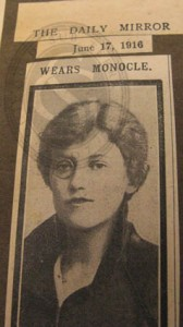 Top part of newspaper cutting showing Elsie Burrell wearing a monocle, 1916