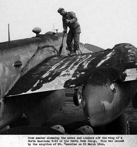 Crew member cleaning the ashes and cinders off the wing of a North American B-25 of the 340th Bomb Group, caused by the eruption of Mt. Vesuvius on 23 March 1944. Image Credit - United States Army Air Force.